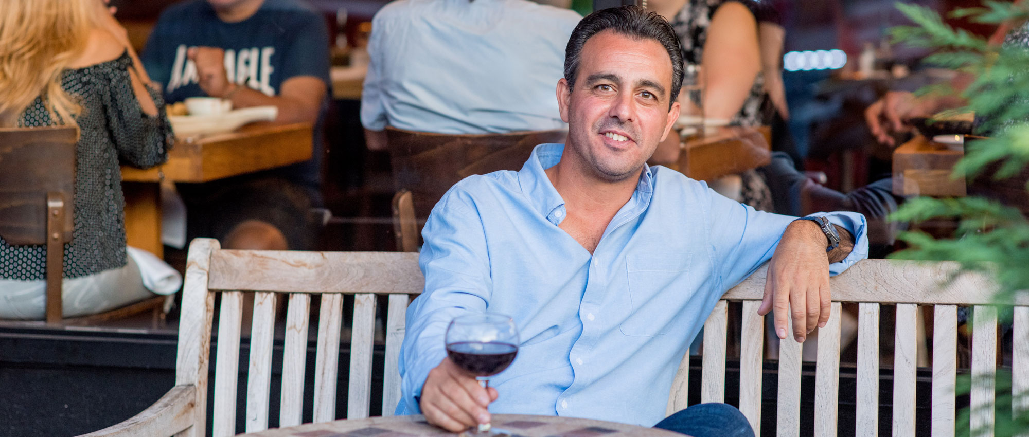 italian man sitting on a wooden bench drinking red wine