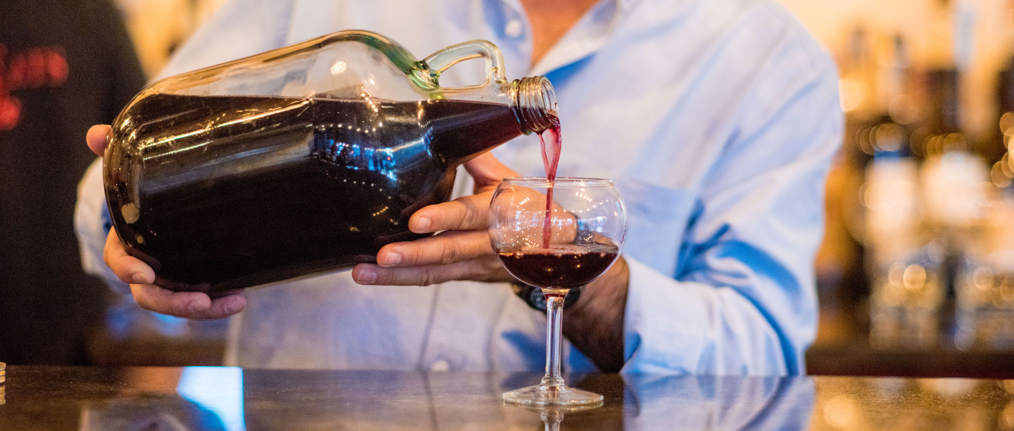 Man pouring wine from a clear glass jug