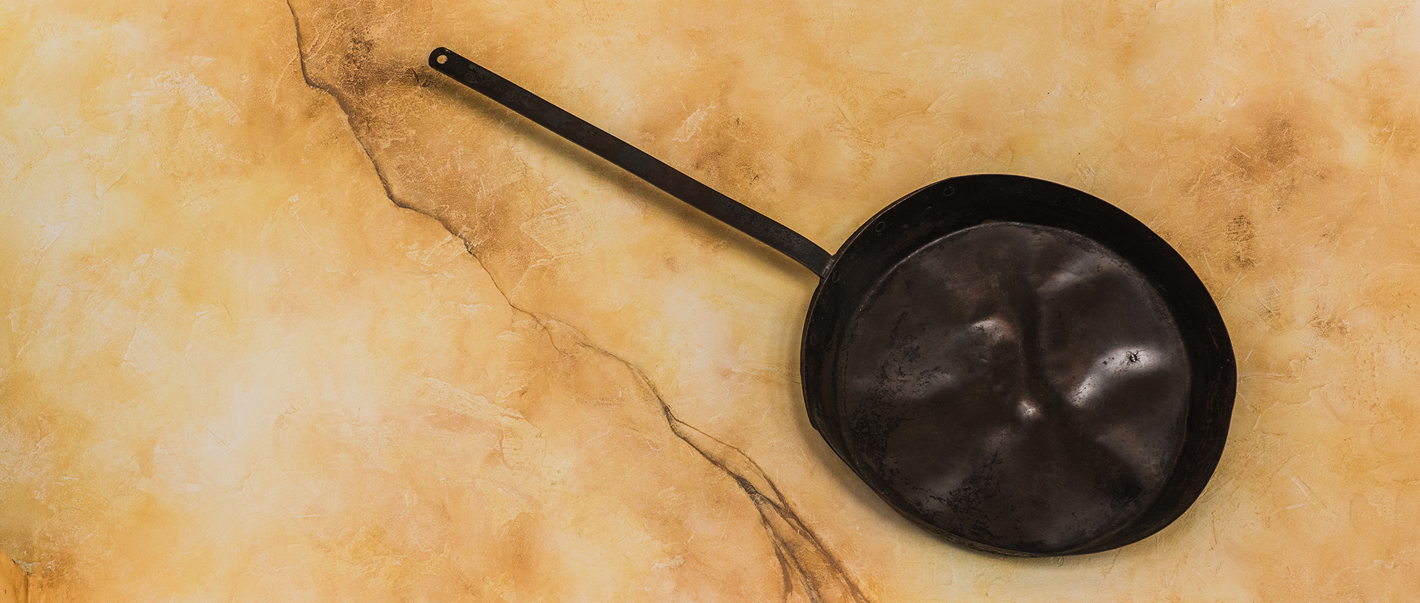 a large, black frying pan with large dents
